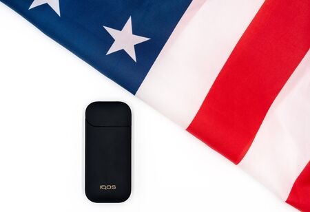 Black IQOS Box, Americas Flag on white background. Iqos electronic cigarette ban concept in the USA. The dependence of adolescents on electronic cigarettes with sweet taste. Russia, Tatarstan, September 08, 2019 Redakční