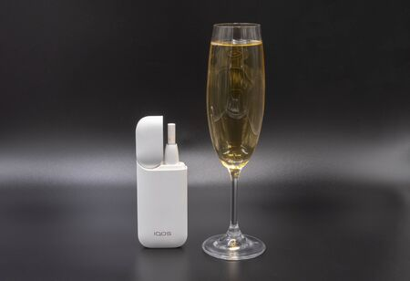 White Iqos device battery with an inserted stick and a glass of white sparkling champagne on a gray background. Russia, Tatarstan, September 08, 2019
