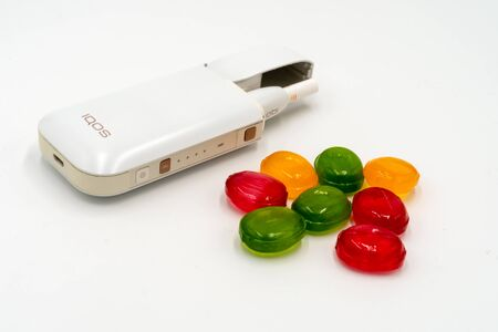 White Box IQOS and multicolored sweet candy lollipops on a white background. The concept of banning electronic cigarettes Iqos in the USA. The dependence of adolescents on electronic cigarettes with a sweet, sweet taste. Russia, Tatarstan, September 08, 2 Redakční
