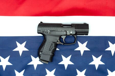 pistol, american flag flat lay on gray background. United States Gun Laws - Guns and weapons.