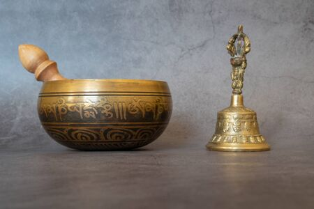 Singing bowl and golden bell close-up, soothing and meditative. Singing bowl with sanskrit engraving pattern and wooden mallet and golden bell of on gray background. Stok Fotoğraf