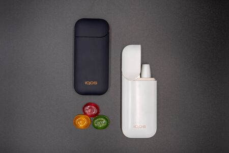 White Iqos device battery, multicolored sweet candy and black Iqos device battery isolated on gray background. Iqos electronic cigarette ban concept in the USA. Russia, Tatarstan, September 08, 2019 Redakční
