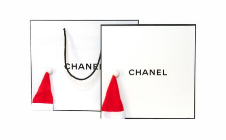 Box, santa claus hat and package Chanel isolated on a white background. Chanel shopper. New Year and Christmas concept. Russia, Tatarstan, September 06, 2019. Redakční