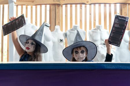 Two Scary little girls in a witch costume looking at camera with a bar menu in hands on a background of old mannequins in a cafe. Halloween party concept. Russia, Tatarstan, September 21, 2019.