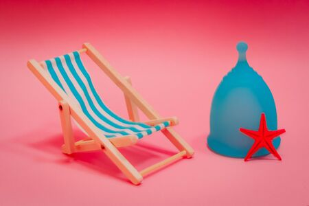 Blue Menstrual cup with a blue deck chair on a pink background. The concept of simplicity and comfort of using the menstrual cup in travel.