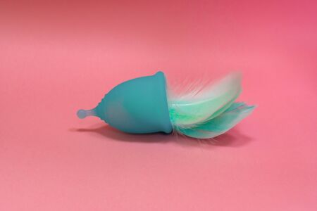 Blue Menstrual cup with blue feathers on pink background. Alternative feminine hygiene product during the period. Women health concept Stok Fotoğraf