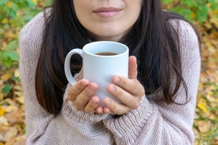 Young woman with pleasure holding mug of hot tea in a hand. Red-haired girl holding her nose, holding a mug of hot tea, on an autumn background. Stockfoto