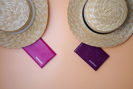 Two womens beach straw boater hats, passports on a beige background. Trip, travel and tourism concept
