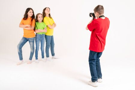 A boy photographer takes pictures of three cute girls in bright T-shirts on a white background in the studio. Young photographer and blogger