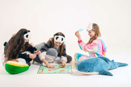 Cute teenage girls in kigurumi and sleep masks are sitting on the floor and playing the monopoly board game. The concept during quarantine is to stay at home and play board games. Russia, Tatarstan, March 21, 2020