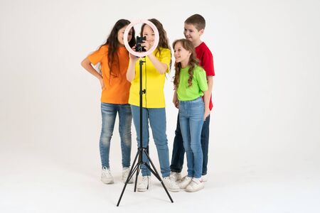 Three teen girls and a boy smiling and shoots a video. Selfies. The phone is mounted on a tripod and the ring lamp shines.