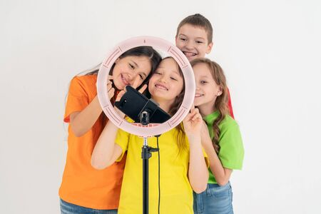 Three teen girls and a boy smiling and shoots a video. Selfies. The phone is mounted on a tripod and the ring lamp shines Banco de Imagens