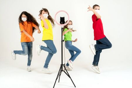 Children dance positively in medical masks. The concept of distance learning during a pandemic. Positive. Movement and sport Reklamní fotografie