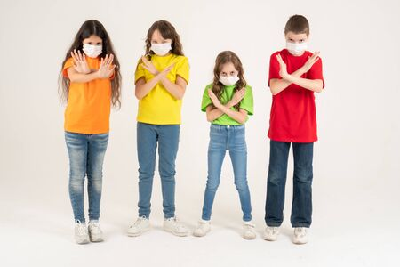 Group of schoolchildren children in colorful T-shirts and medical masks showing crossed hands gesture while looking at the camera over white background. Isolated. Stay at home. Say No to the coronavirus
