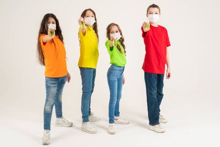 A group of schoolchildren in bright T-shirts and medical masks are holding disinfectants. Stay home and wash my hands. Coronavirus. Season of viral diseases.