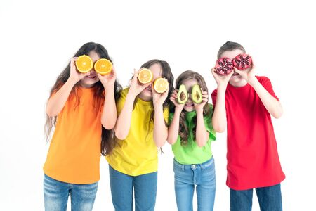 Three girls and a boy using fruits as glasses on a on a white background. Group of happy children with orange, lemon, avocado and pomegranate in hands.