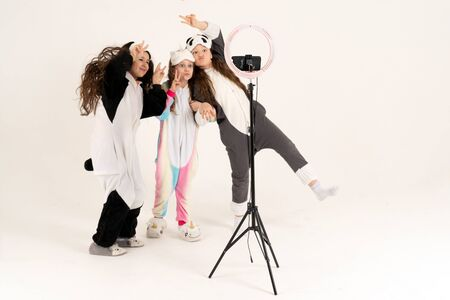 Cute teenage girls in kigurumi and sleep masks smiling and shoots a video. Selfies. The phone is mounted on a tripod and the ring lamp shines.
