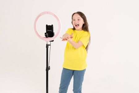 A teenage girl dances and shoots a video. Selfies. The phone is mounted on a tripod and the ring lamp shines Reklamní fotografie
