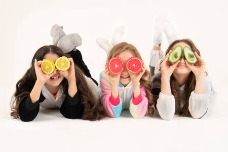 Three girls using fruits as glasses on a on a white background. Group of happy children with grapefruit, lemon, avocado in hands.