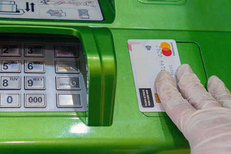 Bank card Mastercard in a hand in a medical protective glove on a background of an ATM. Russia, Tatarstan, March 31, 2020.