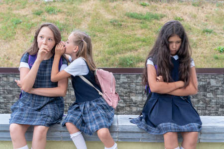 Three schoolgirls are sitting in the schoolyard. One child is offended. The problem of adaptation and communication at school Reklamní fotografie