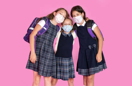 Three happy girls with long hair in school uniforms wearing medical masks. STop coronavirus. Distance learning. Studio photo. Back to school Reklamní fotografie