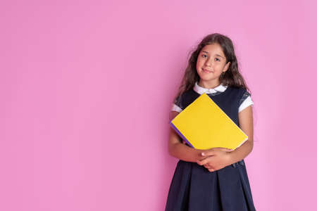 A charming girl with long curly dark hair in a school uniform with a book in her hands on a pink background. Studio photo. Back to school. Reklamní fotografie