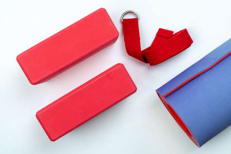 Accessories for yoga and pilates on a white background: support bricks and a belt for proper stretching, a mat