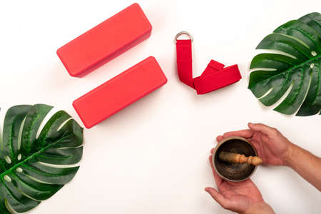 Accessories for yoga and pilates on a white background: support bricks and a belt for proper stretching, a mat. Male hands hold a singing bowl against the background of yoga items Reklamní fotografie