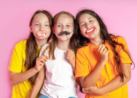 Happy Children hold fake mustache and lips on a pink background. Beauty salon. Hair design salon. Salon photobooth