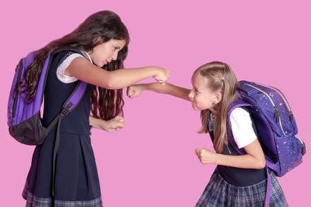 Two schoolgirls in school uniforms are fighting on a pink background Reklamní fotografie