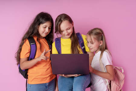 Three schoolgirls are looking at a laptop with enthusiasm. Distance learning concept. Reklamní fotografie