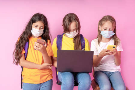 Three schoolgirls in medical masks are holding smartphones and a laptop. Distance learning concept. Back to school. Studio photo. Reklamní fotografie