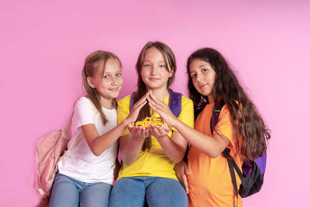 Three girls schoolgirls are holding a toy school bus in their hands. The concept of the safety of children at school. Back to school. Studio photo.