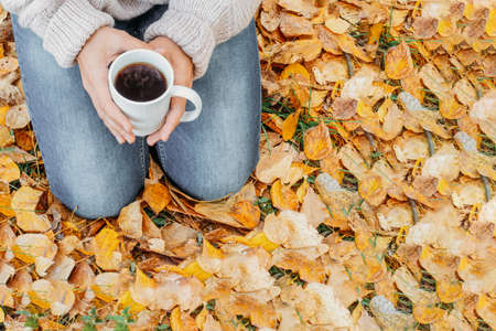 Cup of tea in hand outdoor. Walk in the autumn forest .