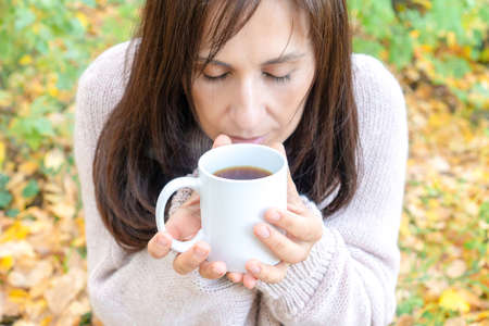 Middle-aged woman eyes closed with pleasure holding mug of hot tea in a hand in the autumn forest. close-up Reklamní fotografie