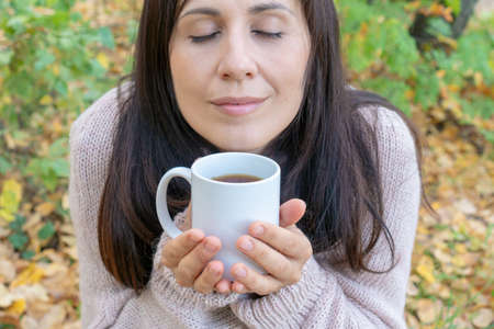 Middle-aged woman eyes closed with pleasure holding mug of hot tea in a hand in the autumn forest. close-up.
