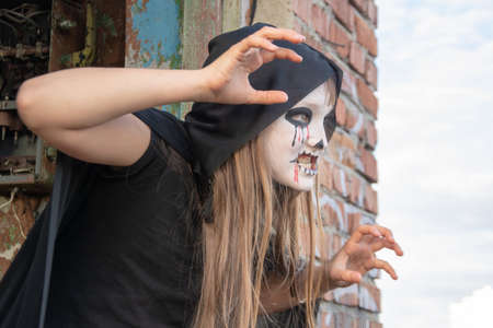a little teenager girl in a zombie costum against a brick wall. Halloween and day of the dead concept