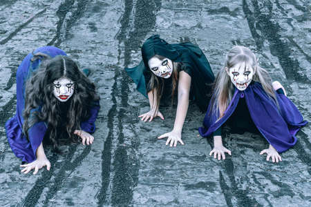 Kids with face-paint and Halloween costumes on the roof of an abandoned and old building