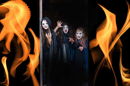 Kids with face-paint and Halloween costumes a fire is burning on a black background Reklamní fotografie