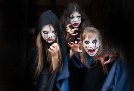 Kids with face-paint and Halloween costumes on a black background Reklamní fotografie