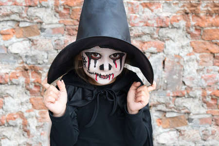 Scary little girl in a witch costume smiles on brick wall background. Halloween and day of the dead concept