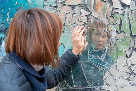 woman looks in a broken mirror and shows her hand on a mirror. International day for the elimination of violence against women.