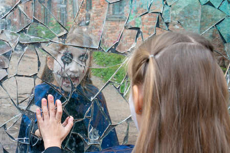 Young girl looks in a broken mirror .