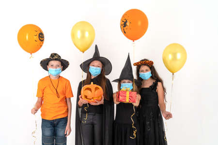 A group of children in medical masks and Halloween costumes. The Halloween concept and the 2020 pandemic.