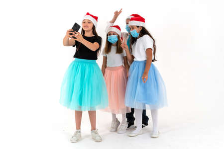 Three teen girls and a boy smiling and shoots a video. Christmas online greetings and meetings Reklamní fotografie