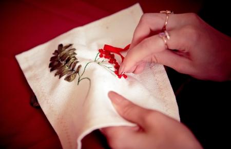 trabajo manual: Cintas de bordado. Trabajo hecho a mano. CU de la mano de la mujer con una aguja