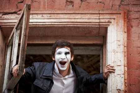 joyfully: Portrait of a Man ​​mime  Joyfully shouts, throwing an old wooden box
