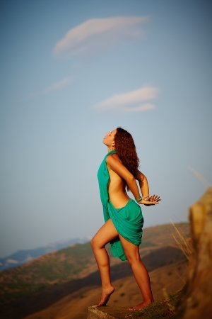Beautiful girl standing on a precipice  One leg is slightly raised for a step forward  Hands behind his back wound photo