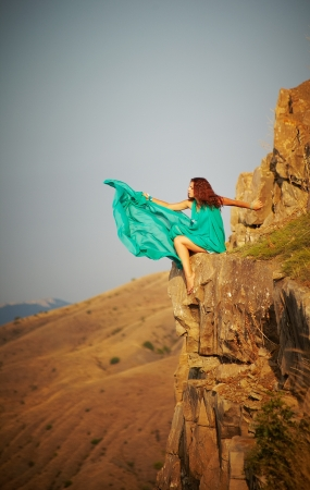 Girl sitting on the precipice of a cliff  He throws the fabric into the abyss photo